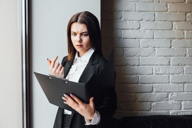 Schitterende dame met omslag bij handen die voor examen voorbereidingen treffen!