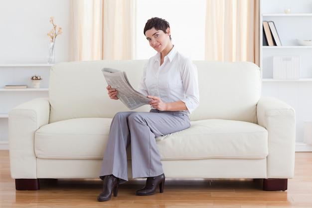 Schitterende donkerbruine onderneemster die het nieuws leest