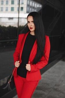 Schitterende donkerbruine vrouw in een rood kostuum