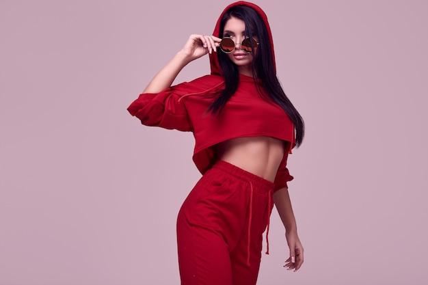 Schitterende donkerbruine vrouw in manier rode hoodie in studio
