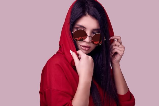 Schitterende donkerbruine vrouw in mode rode hoodie