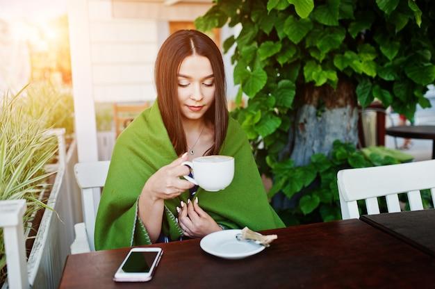 Schitterende donkerbruine vrouwenzitting op de lijst in de plaid van de koffiedekking met kop van koffie.