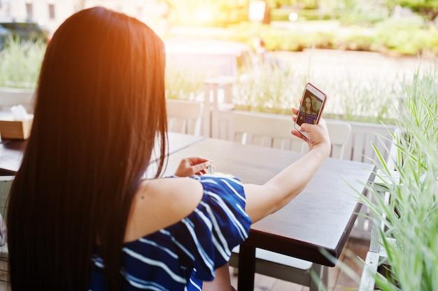Schitterende donkerbruine vrouwenzitting op de lijst in koffie met kop van koffie en het maken van selfie.
