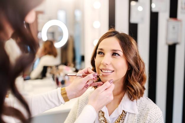 Schitterende donkerbruine zitting bij schoonheidssalon terwijl make-upkunstenaar lip liner crayon op lippen zet.