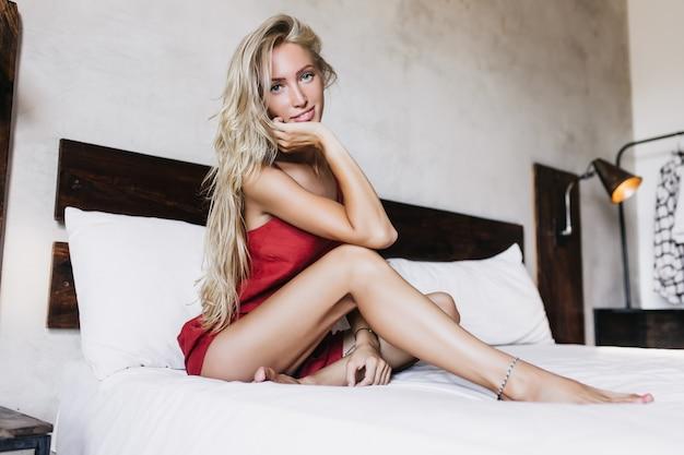 Schitterende gebruinde dame zittend op bed in pyjama. dromerige langharige vrouw poseren in de ochtend in haar kamer.
