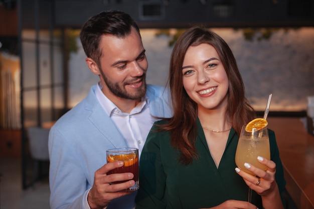 Schitterende gelukkige vrouw die aan de camera glimlacht, die van avondje uit met haar man geniet bij cocktailbar.