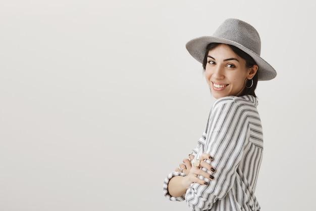 Schitterende gelukkige vrouw in stijlvolle hoed glimlachen, klaar voor vakantie