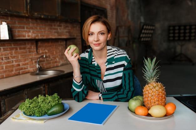 Schitterende gezonde jonge vrouw die appel in haar moderne zolderkeuken eet. fitnesstrainer.