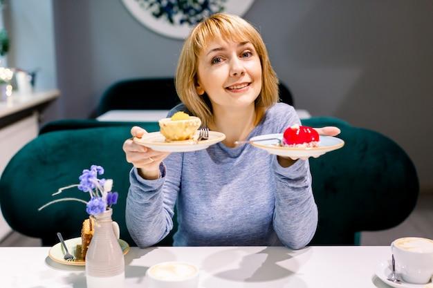 Schitterende glimlachende jonge vrouw die cake eet en koffie drinkt bij een cafetaria. vrouw die met twee platen van cakes bij de lijst zit