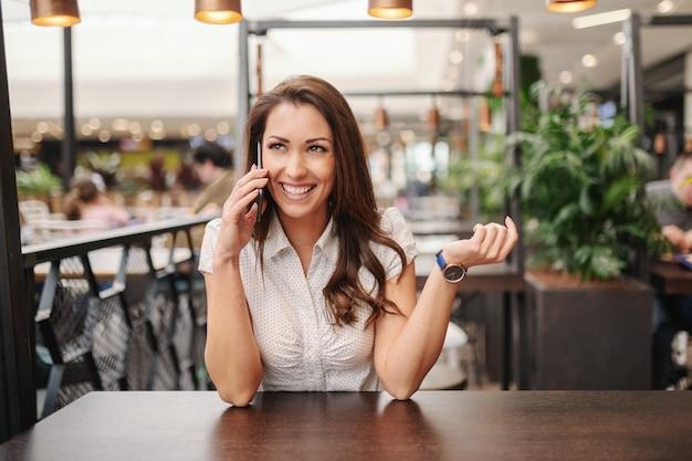 Schitterende glimlachende kaukasische donkerbruine zitting bij koffiewinkel en het spreken op de slimme telefoon.