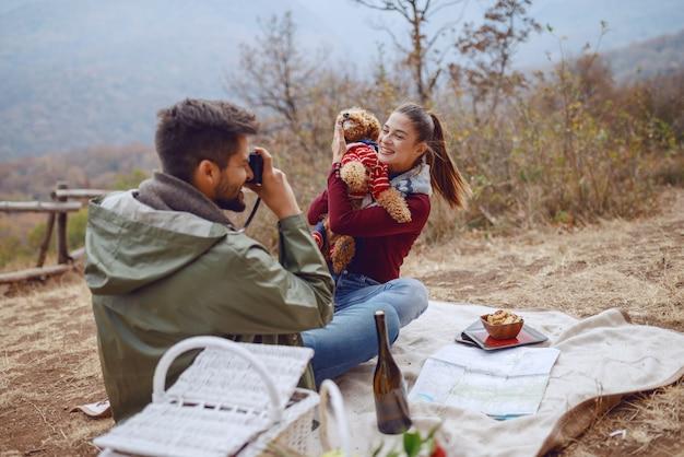 Schitterende glimlachende kaukasische donkerbruine zitting op deken en het stellen met haar hond terwijl haar vriend die foto van hen neemt.