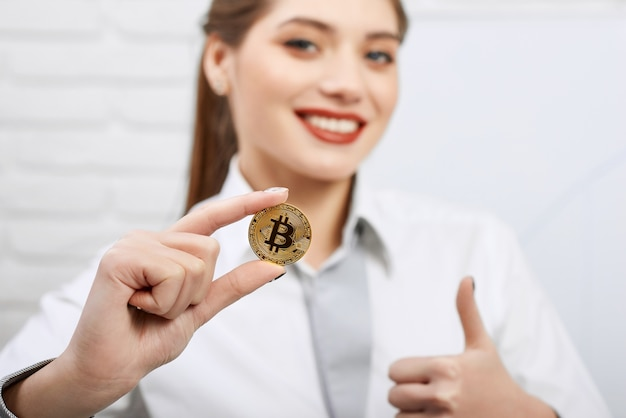 Schitterende glimlachende vrouw die gouden bitcoin en het tonen van duimen tegenhouden