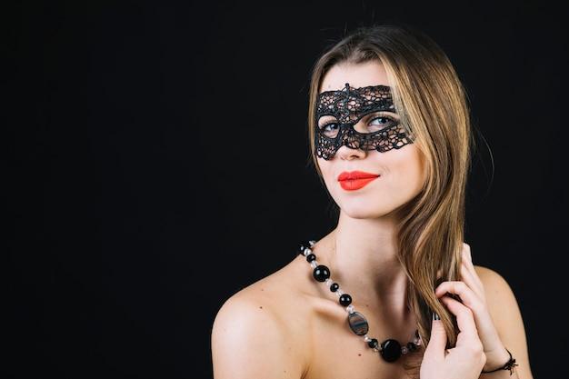 Schitterende glimlachende vrouw in maskerade carnaval masker op zwarte achtergrond