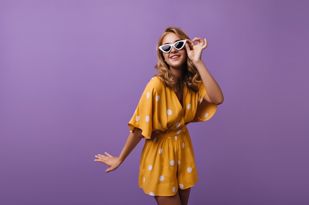 Schitterende goed geklede vrouw die op paars glimlacht. portret van betoverende dame in gele kledij.