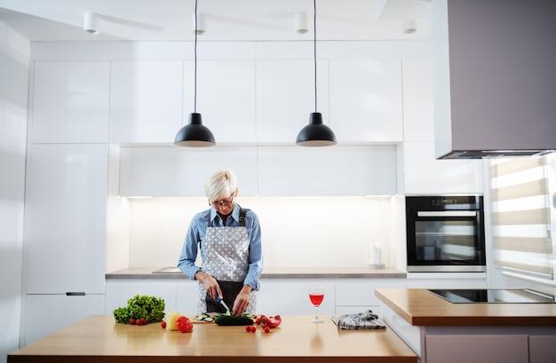 Schitterende hogere vrouw in schort het winkelen komkommer en het maken van salade terwijl status in keuken