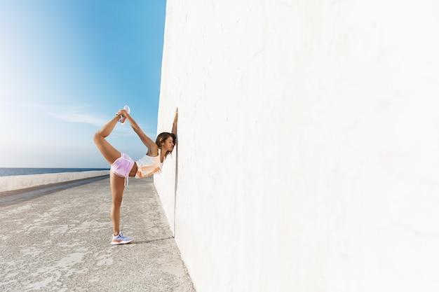 Schitterende jonge blanke vrouw die ochtendgymnastiek doet die betonnen kademuur leunt, been opheft