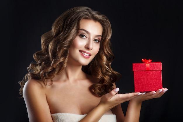 Schitterende jonge donkerbruine vrouw met rode giftdoos. perfecte make-up. valentijnsdag brunette dame headshot