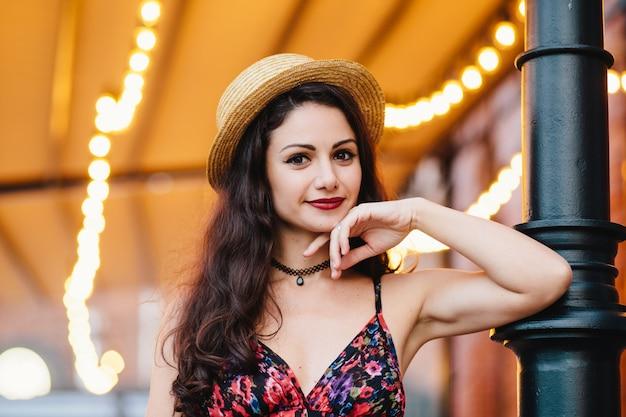 Schitterende jonge elegante vrouw met aantrekkelijke uitstraling poseren op terras, gekleed in strohoed en zomerjurk
