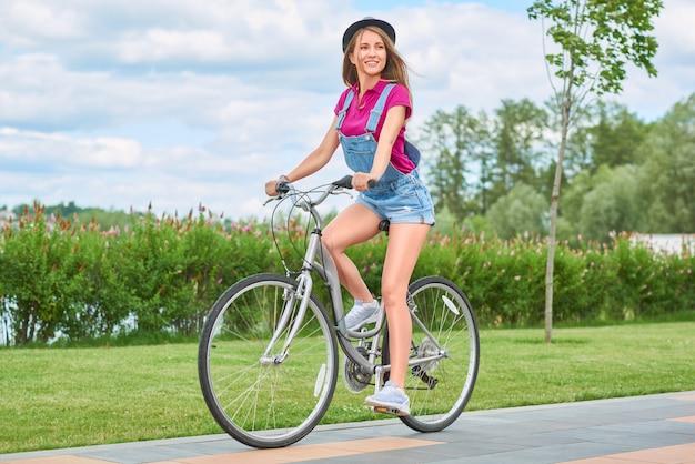 Schitterende jonge vrolijke vrouw die haar fiets berijden bij park glimlachen die rond vreugdevol gelukemoties de levensstijlactiviteit geschiktheidsrecreatie kijken van gelukemoties.