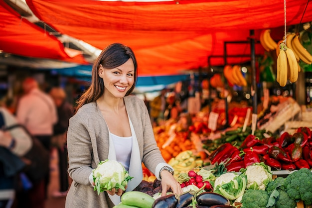 Schitterende jonge vrouw bij landbouwersmarkt. verse bloemkool vasthouden.