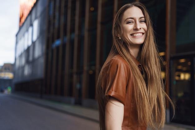 Schitterende jonge vrouw die bij camera glimlacht, zich achter omdraait en glimlacht.