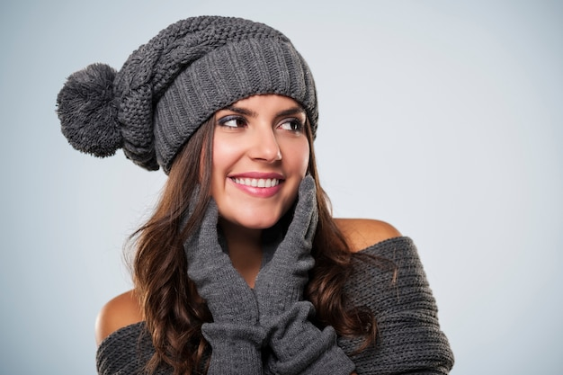 Schitterende jonge vrouw die de winterkleding draagt die exemplaarruimte bekijkt