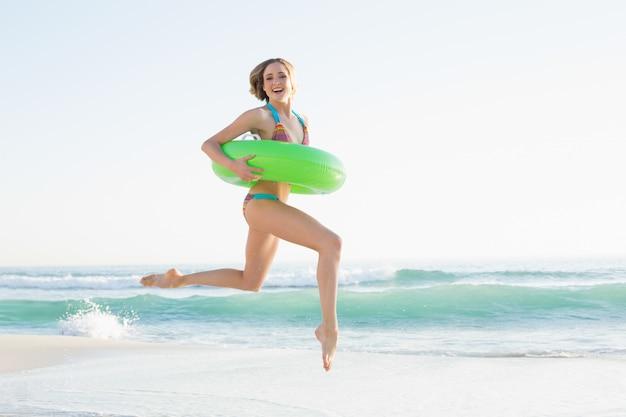 Schitterende jonge vrouw die een rubberring houdt terwijl het springen op strand