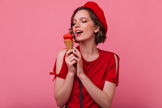 Schitterende jonge vrouw die in rode kleren roomijs eet. verfijnd frans vrouwelijk model poseren met dessert.