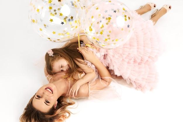 Schitterende jonge vrouw die lage hals strapless kleding draagt die verjaardag met haar dochter viert