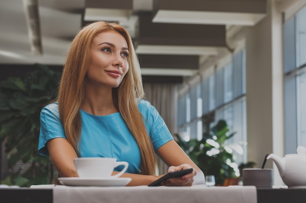 Schitterende jonge vrouw die ontbijt heeft in het restaurant