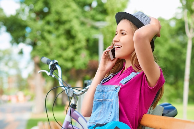 Schitterende jonge vrouw die opgewekt kijken terwijl het spreken op de telefoon die bij het lokale van het de emotiesgeluk van het park goede nieuws van de de schoonheidslevensstijl van de nieuwsrecreatie zorgeloze mobiliteitstechnologie dragercommunicatie ontspannen.