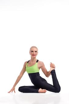 Schitterende jonge vrouw die yoga beoefent, zittend op de vloer