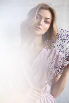 Schitterende jonge vrouw in een mooie jurk met bloemen