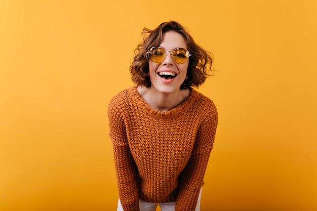 Schitterende jonge vrouw in grappige ronde glazen die aan camera lachen