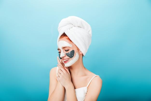 Schitterende jonge vrouw in handdoek die zich voordeed op blauwe achtergrond. studio die van wit meisje met gezichtsmasker is ontsproten.