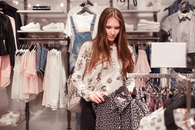 Schitterende jonge vrouw in het zoeken naar nieuwe jurk in fashion boetiek.