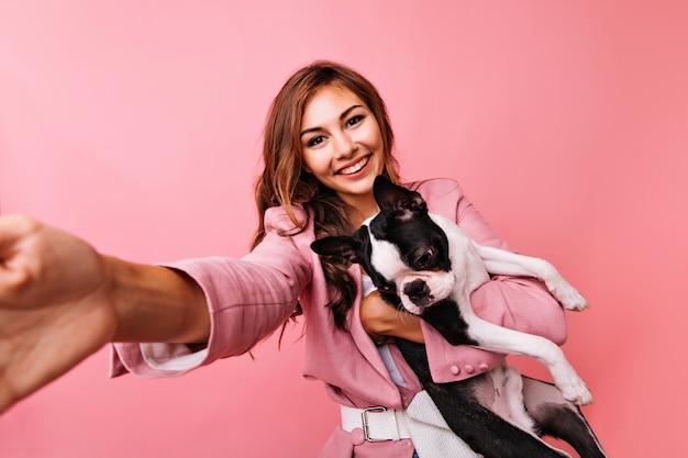 Schitterende jonge vrouw in roze jasje dat foto van zichzelf met hond neemt. mooie blanke meisje speelt met bulldog.