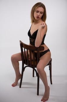 Schitterende jonge vrouw in zwart kanten ondergoed, zittend op een stoel.