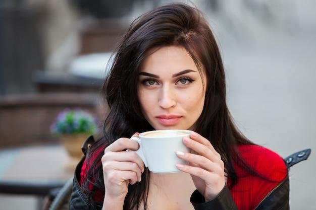 Schitterende jonge vrouw met kop koffie in stadsstraat
