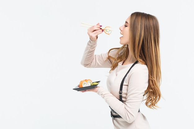 Schitterende, jonge vrouw stopt stuk broodje in mond