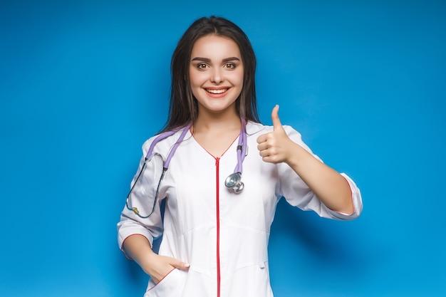 Schitterende jonge vrouwelijke arts maakt okaysign, op blauw. jonge geneeskunde.
