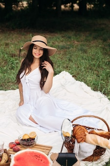 Schitterende kaukasische vrouw met bakkerij. stockfoto portret van een mooie brunette vrouw in zomer hat