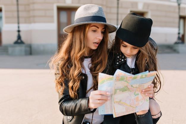Schitterende langharige vrouw die kaart met verwarde gezichtsuitdrukking bekijkt. portret van een klein meisje met een zwarte hoed, die met haar moeder een route plant door een onbekende stad.