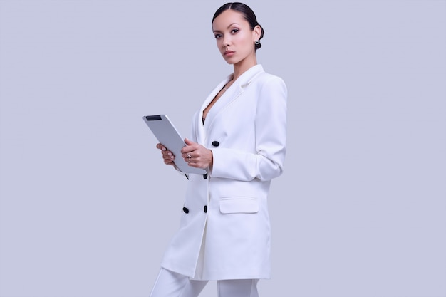 Schitterende latijnse vrouwen in mode wit pak met digitale tablet