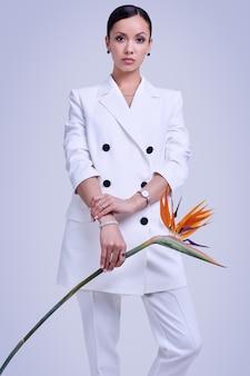 Schitterende latijnse vrouwen in mode wit pak met exotische bloem