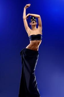 Schitterende mannequin die hoogste en lange zwarte rok en batman masker draagt