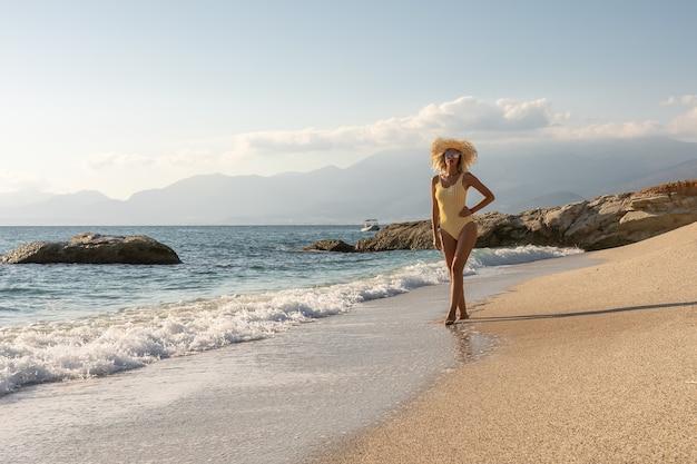 Schitterende mannequin in zwembroek op een zandstrand.