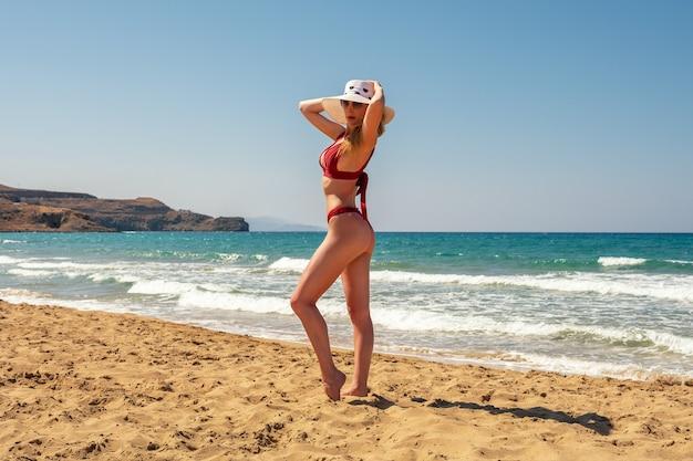 Schitterende mannequin in zwembroek op een zandstrand