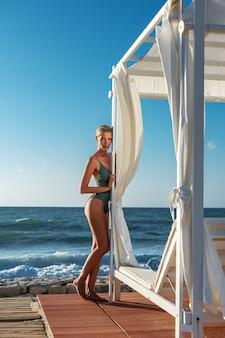 Schitterende mannequin in zwembroek poseren op het strand