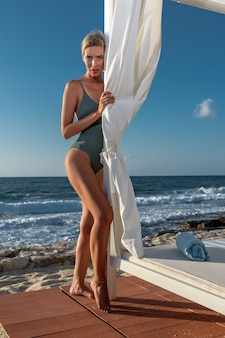Schitterende mannequin in zwembroek poseren op het strand.